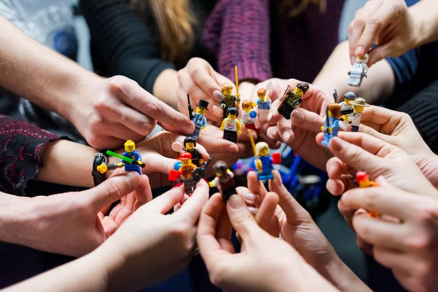 mains qui tiennent des pièces de lego