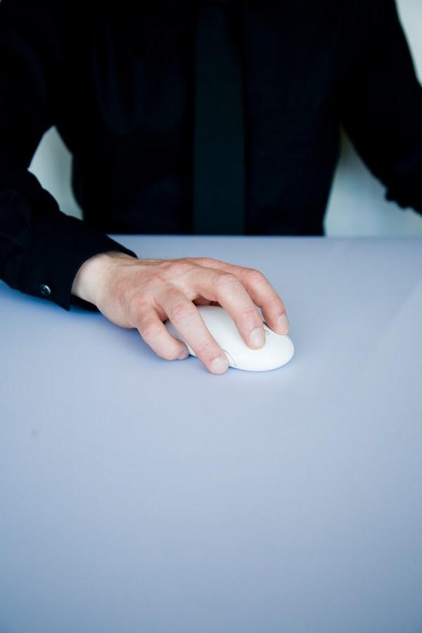 personne qui tient une souris d'ordinateur