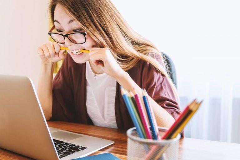 femme contrariée devant son ordinateur qui mord un crayon