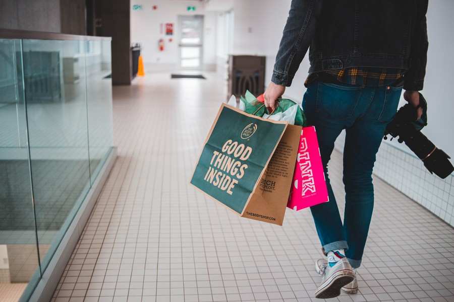 homme dans un centre commercial qui porte des sacs de shopping