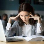 Femme au bureau qui essaie de se concentrer devant son ordinateur