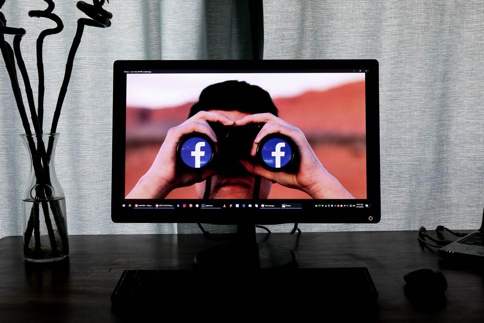 écran d'ordinateur avec en fond d'écran un homme avec des jumelles Facebook