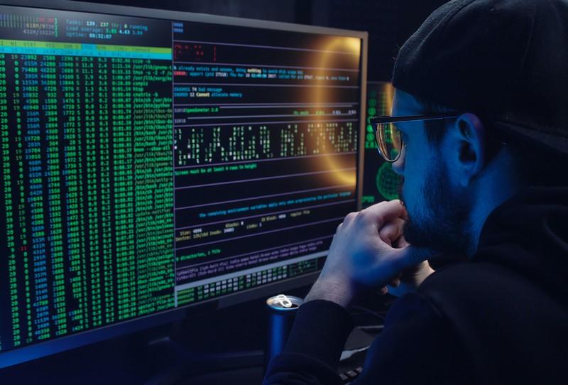 homme devant l'écran d'ordinateur qui affiche des lignes de code