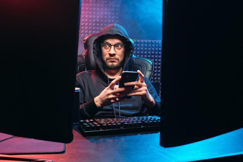 homme devant son ordinateur unportable à la main qui regarde un des deux écrans l'air inquiet