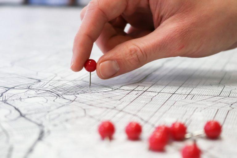 main qui place une épingle sur une carte