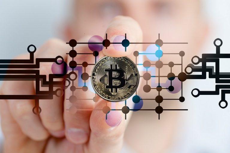 main qui tient un pièce de bitcoin