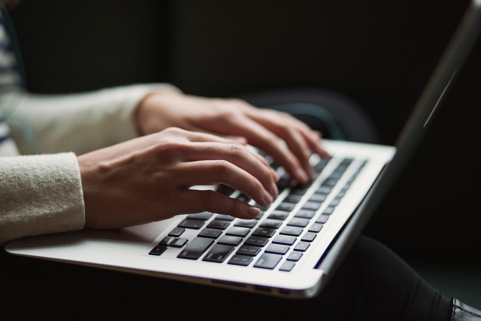 mains d'une femme qui tapent sur les touches d'un clavier d'ordinateur