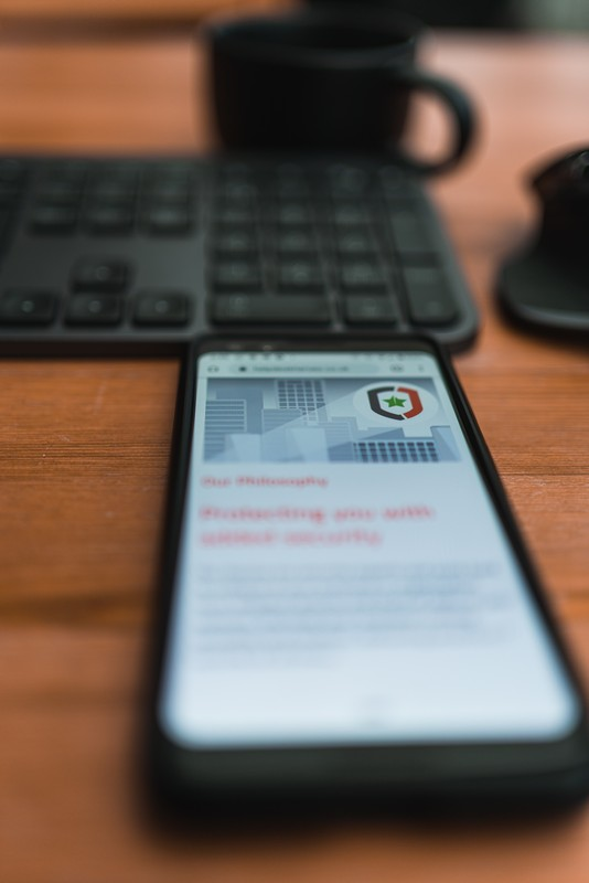 portable avec une application antivirus posé sur une table de bureau devant le clavier