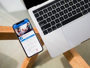 portable connecté à Facebook posé à côté d'un pc portable