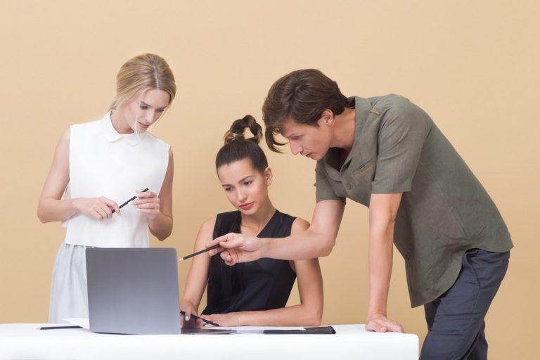 trois personnes qui étudient des données sur un ordinateur